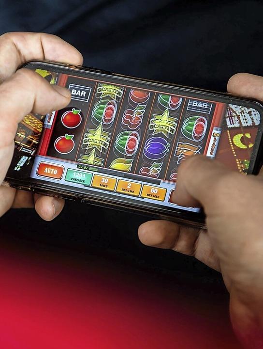 Auf einem Smartphone spielt ein Mann ein Online-Spiel.  | Foto: Sina Schuldt (dpa)