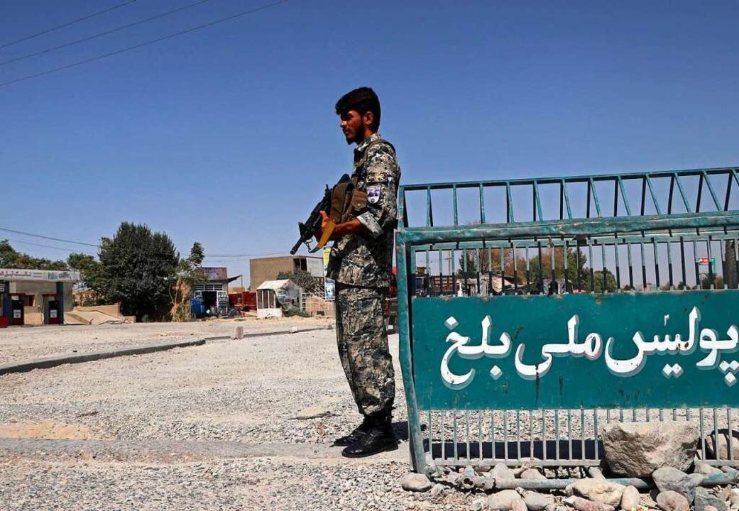 Ein afghanischer Polizist stand vor we...eflüchteten stammen dort aus der Nähe.  | Foto: Mirwais Bezhan (dpa)