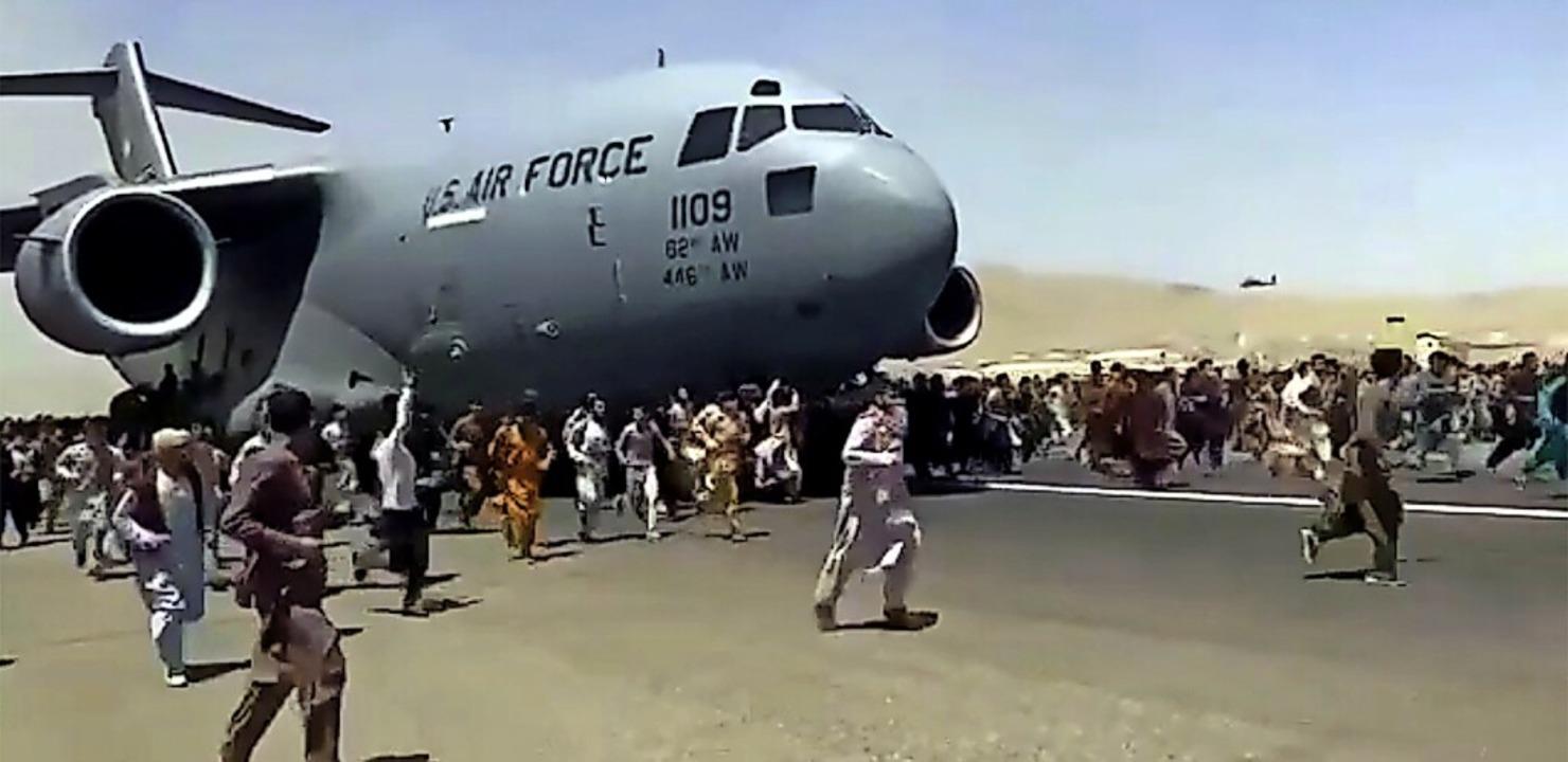 Hunderte Menschen laufen neben einer U...er Flugzeuge zu kommen, um zu fliehen.  | Foto: Uncredited (dpa)