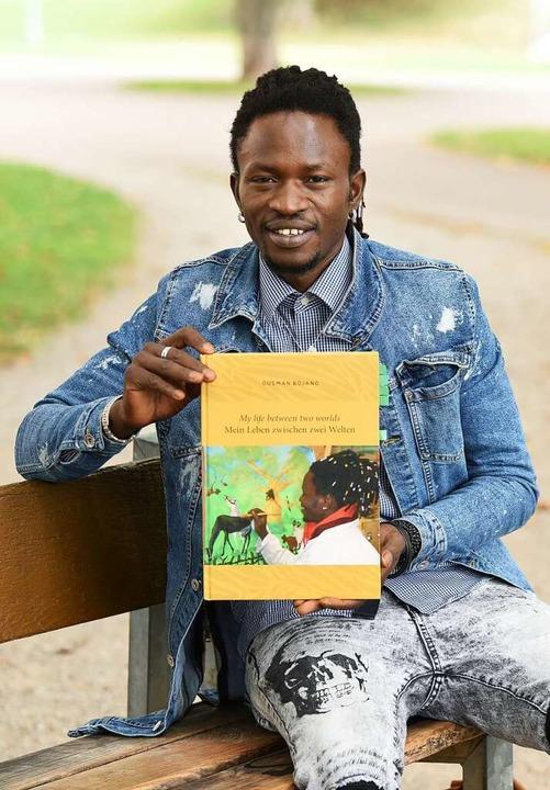 Ousman Bojang präsentiert das Buch mit seinen Bildern.     Foto: Rita Eggstein