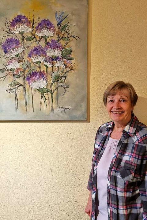 Christa Framke steht neben einem Bild ihres verstorbenen Mannes.  | Foto: Nadine Klossek-Lais