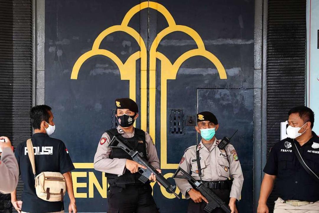 Polizisten bewachen den Haupteingang d...d acht weitere schwer verletzt worden.  | Foto: Tatan Syuflana (dpa)