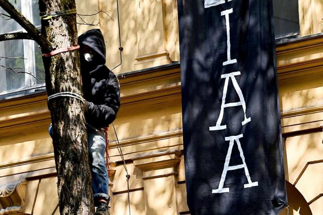 Ein Protestteilnehmer ist vor einem be... in München auf einen Baum geklettert.  | Foto: Peter Kneffel (dpa)