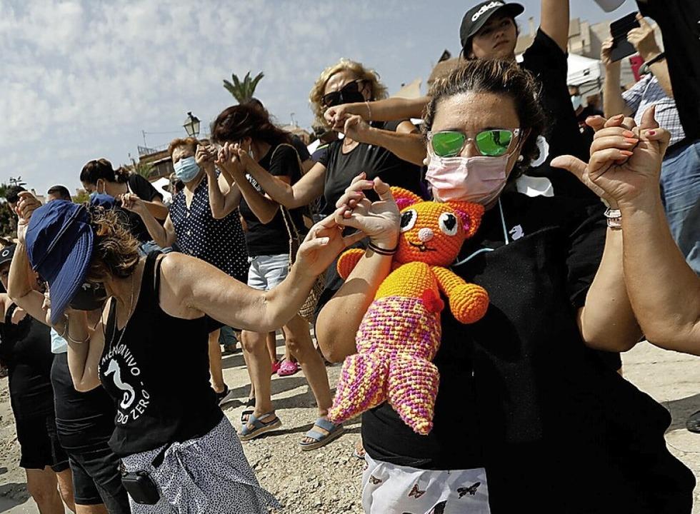 Ende August bildeten Demonstranten ein...mutzung des Mar Menor zu protestieren.  | Foto: Edu Botella (dpa)