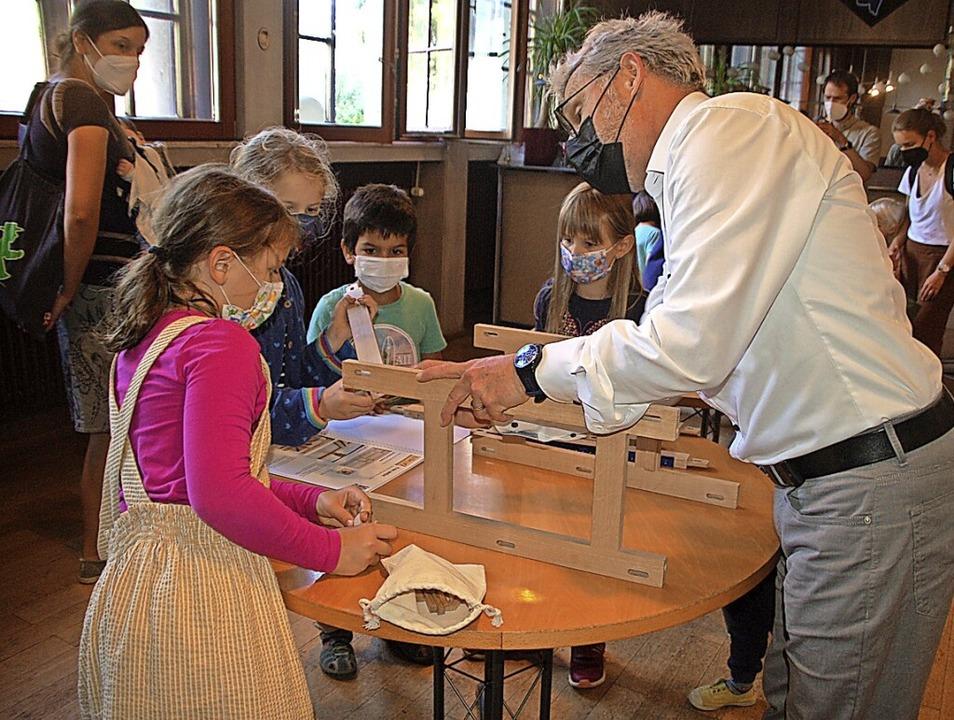 Rainer Marbach (rechts) baut mit Kindern ein Orgelmodell.     Foto: Petra Wunderle