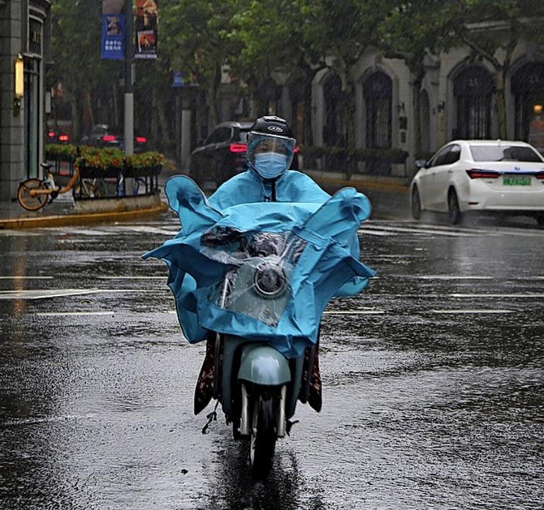 Ein Anwohner fährt durch Pfützen.    Foto: Chen Si (dpa)