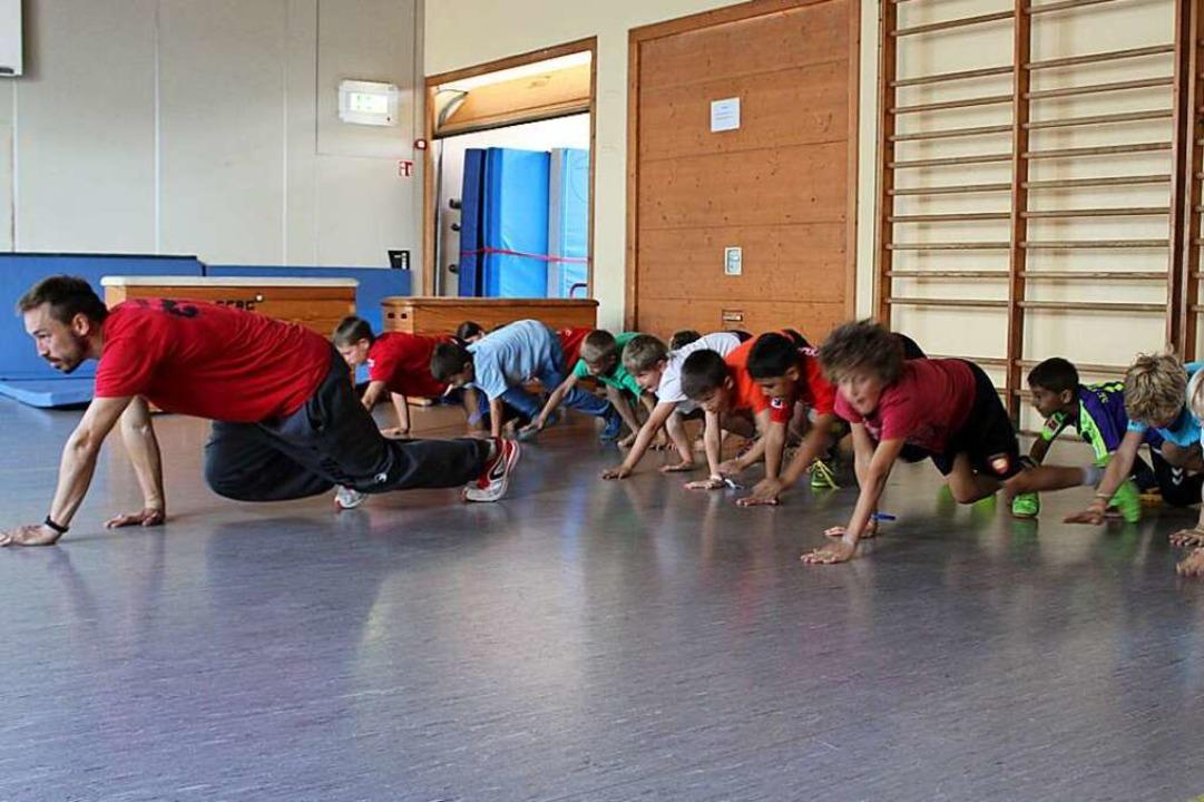 Kamil Feucht vom Sportverein Eschbach zeigt den Kindern den Animal-Walk.  | Foto: Nina Herrmann