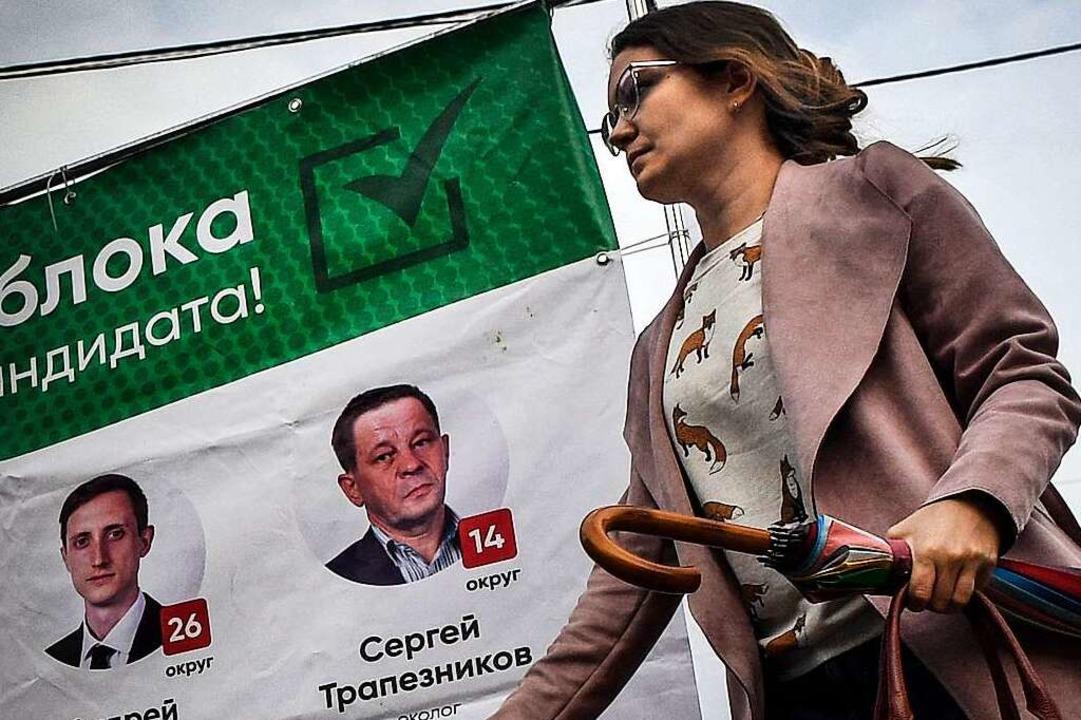 Eine Frau läuft in Tomsk an Plakaten der liberalen Jabloko-Partei vorbei.    Foto: ALEXANDER NEMENOV