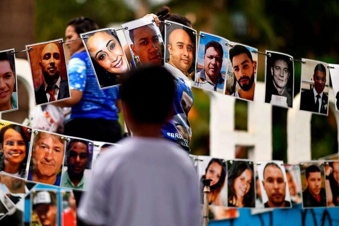 Ein Jahr nach dem Dammbruch erinnern A...mit Fotos an die Opfer des Dammbruchs.  | Foto: DOUGLAS MAGNO (AFP)