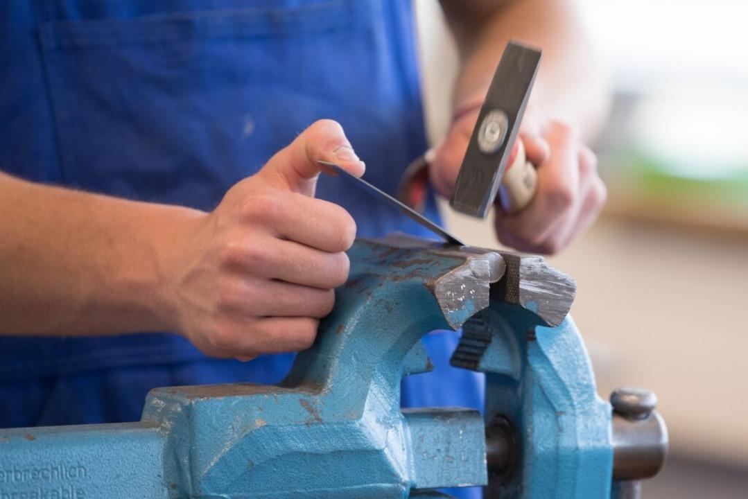 Ein Auszubildender arbeitet mit einem Hammer an einem Schraubstock. (Symbolbild)  | Foto: Sebastian Kahnert (dpa)