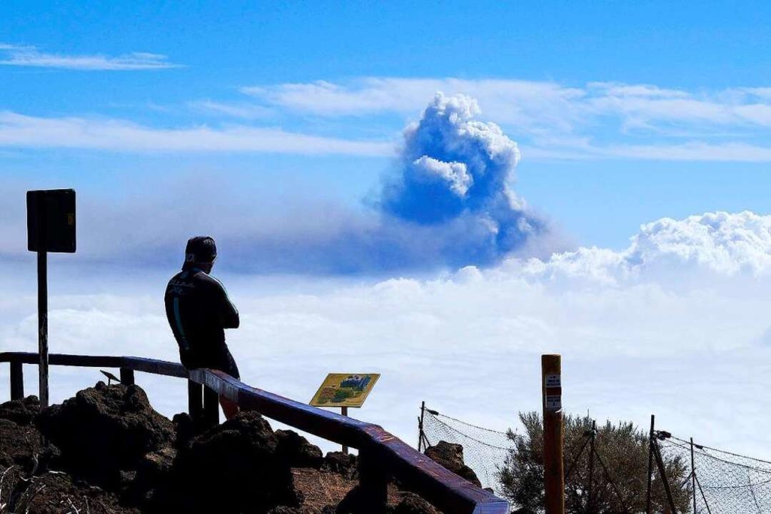 Ein Mann beobachtet aus der Ferne in R...Rauchwolke, die aus dem Vulkan steigt.  | Foto: Europa Press (dpa)