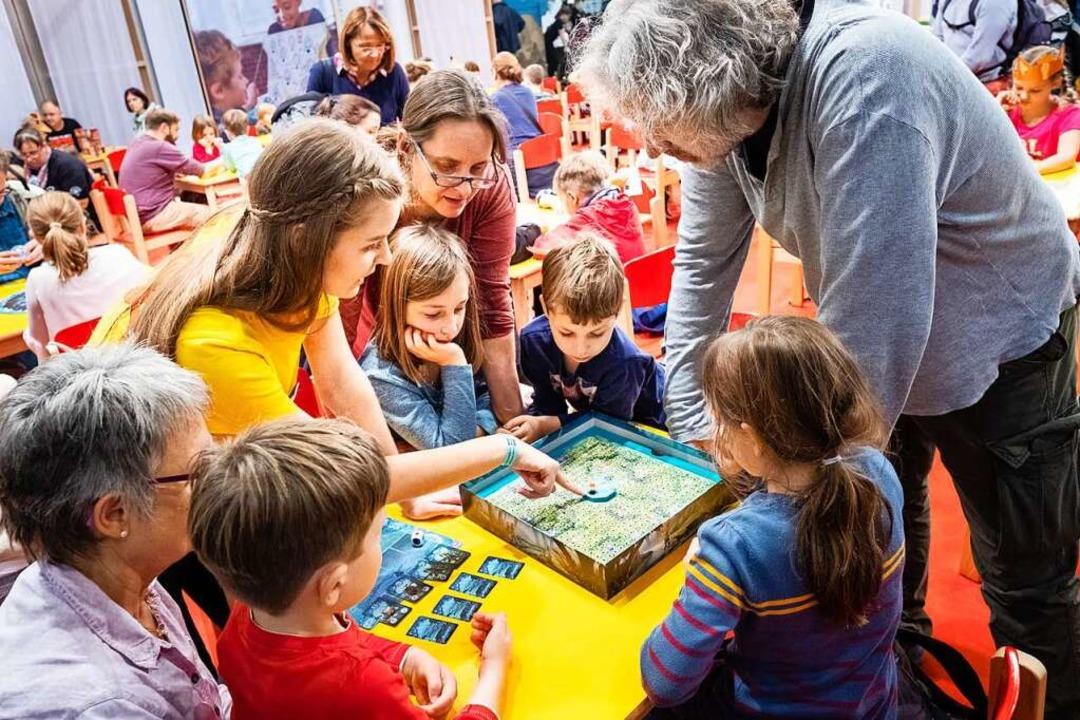Groß und klein spielen zusammen ein Brettspiel.    Foto: - (dpa)